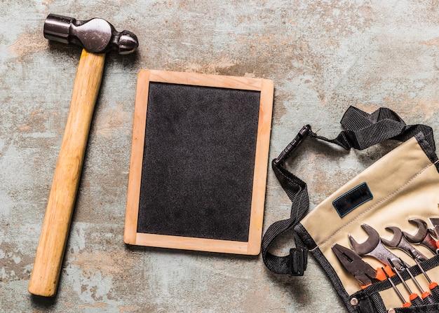 Divers outils dans le sac à outils près d'ardoise et de marteau sur le bureau en bois de rouille Photo gratuit