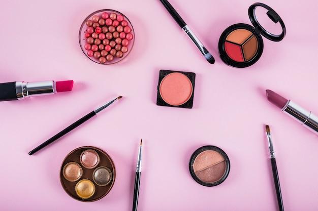 Divers produits de maquillage et cosmétiques sur fond rose Photo gratuit