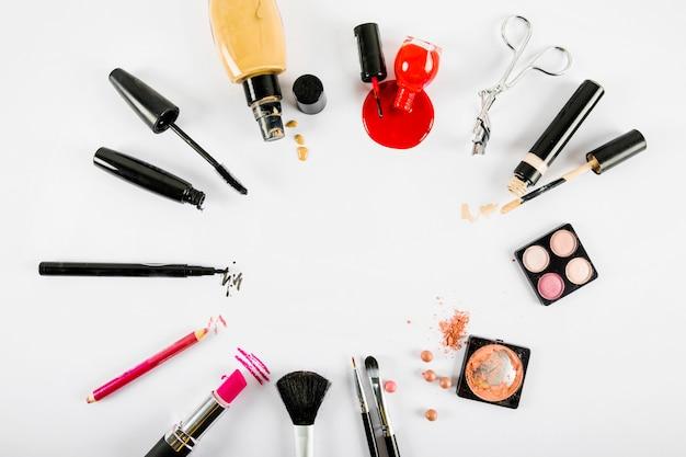 Divers produits de maquillage formant un cadre circulaire sur fond blanc Photo gratuit