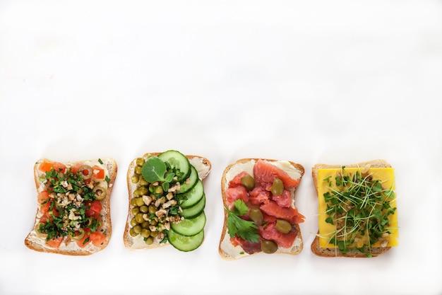 Divers Sandwichs Au Saumon Salé, Concombres, Tomates, Pois Verts, Olives, Pousses Sur Une Plaque Blanche. Photo Premium
