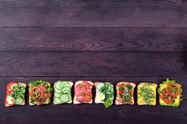 Divers Sandwichs Sur Du Pain Grillé Avec Du Saumon, Des Germes, Des Légumes, Des œufs Se Trouvent Dans Une Rangée Sur Un Bois Brun. Photo Premium