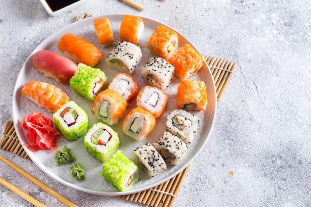 Divers sushi frais et délicieux sur l'ardoise blanche avec des bâtons en bois, sauce sur fond de pierre clair Photo Premium