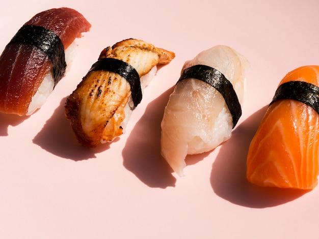 Divers sushis sur fond rose Photo gratuit