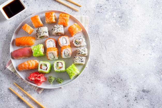 Divers sushis sur plaque avec des bâtons en bois, sauce sur fond de pierre clair Photo Premium