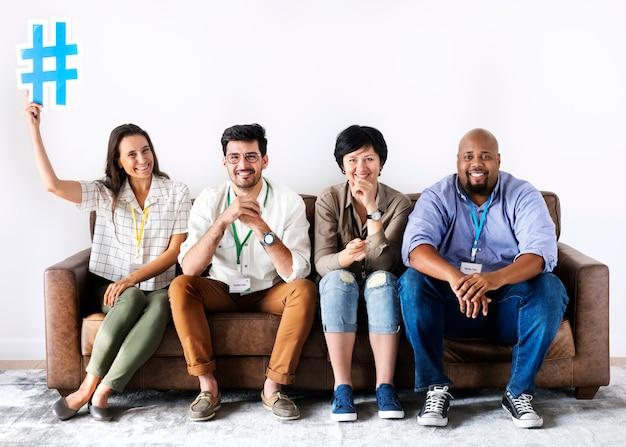 Divers travailleurs assis ensemble femme tenant l'icône de hashtag Photo Premium