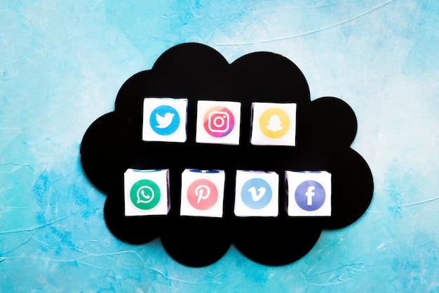 Diverses boîtes d'icônes de médias sociaux sur un nuage noir sur fond bleu Photo gratuit