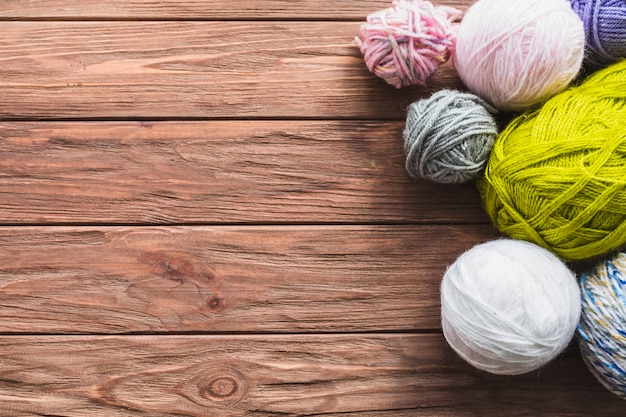 Diverses boules colorées de fils sur fond en bois Photo gratuit