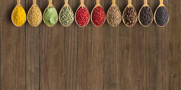 Diverses épices et herbes dans des cuillères en bois. condiments sur millésime Photo Premium