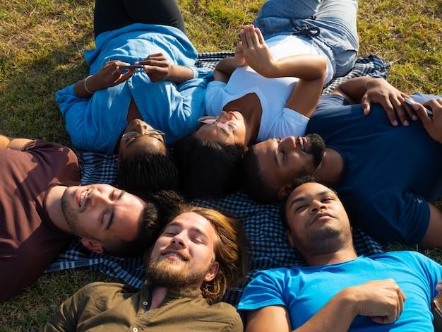 Diverses équipes d'amis se détendant dans un parc Photo gratuit