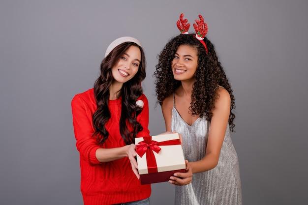 Diverses Femmes Heureuses Avec Boîte-cadeau Avec Ruban Portant Chapeau De Noël Isolé Sur Gris Photo Premium
