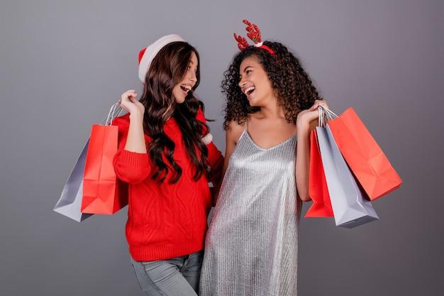 Diverses femmes heureuses avec des sacs colorés, portant un chapeau de noël rouge isolé sur gris Photo Premium