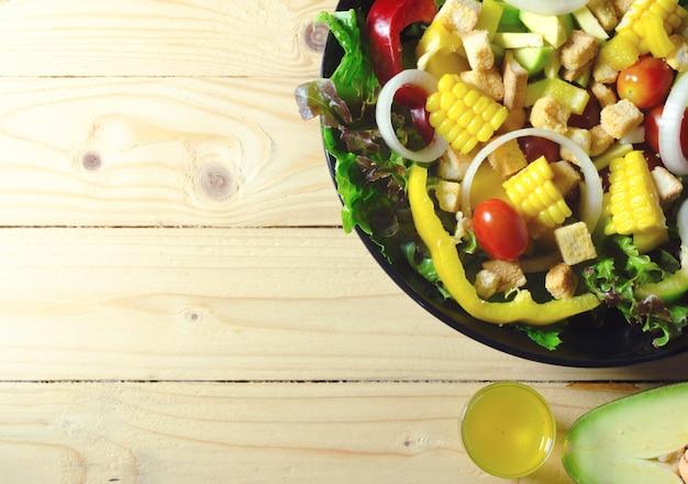 Diverses feuilles de salade fraîche à la tomate dans un bol sur fond en bois Photo Premium