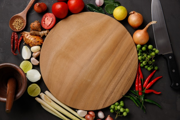 Diverses herbes et ingrédients à cuisiner sur un fond sombre. Photo Premium