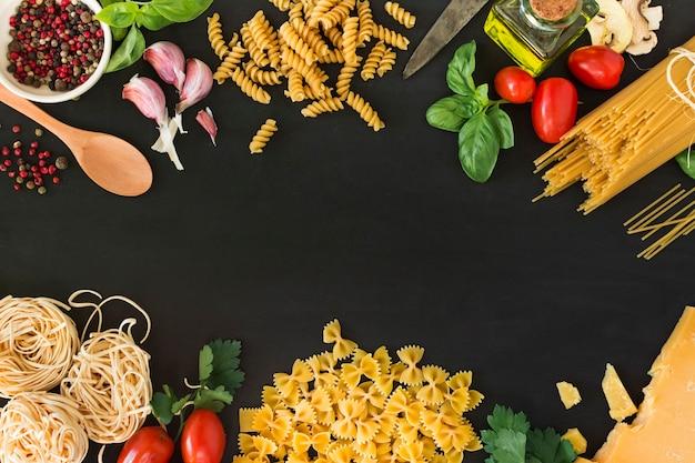 Diverses pâtes crues avec des ingrédients sur fond noir Photo gratuit