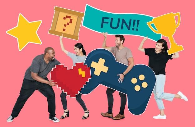 Diverses personnes ludiques tenant des icônes de jeu Photo gratuit