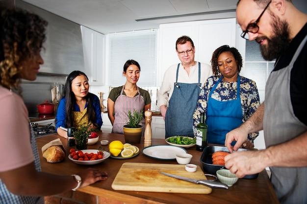 Diverses personnes rejoignant un cours de cuisine Photo Premium