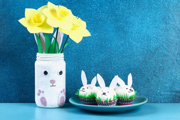 Diy lapin des oeufs de pâques sur fond bleu. idées cadeaux, décor pâques, printemps. fait main. Photo Premium