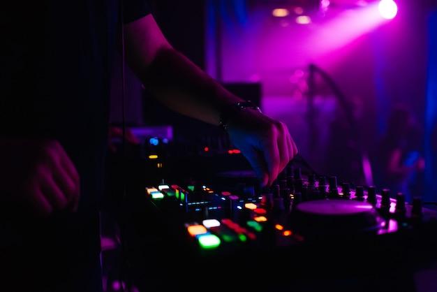 Le dj contrôle la musique en boîte de nuit en déplaçant les contrôleurs sur le tableau de musique Photo Premium