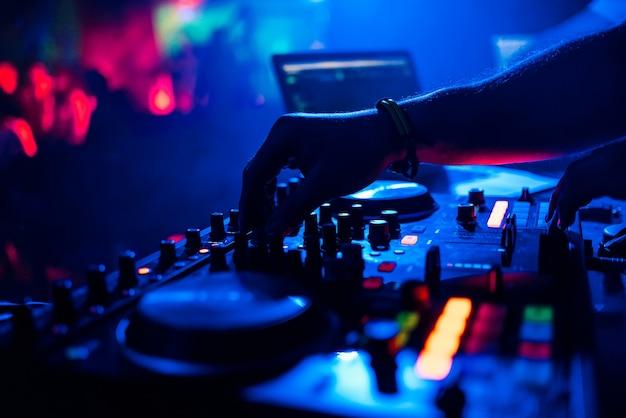 Dj mixant musique déplaçant les contrôleurs sur la table de mixage en boite de nuit Photo Premium