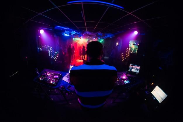 Dj Mixe La Musique Dans Une Discothèque Avec Des Gens Qui Dansent Photo Premium