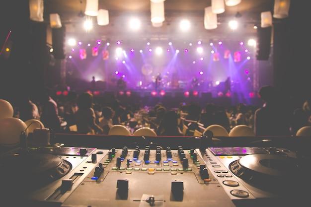 Dj qui tourne, mixe et gratte en boîte de nuit, lumières stroboscopiques et brouillard Photo Premium