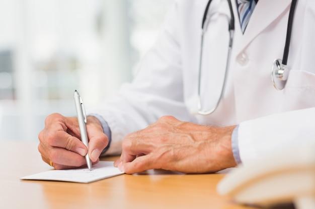 Docteur assis à son bureau en écrivant une ordonnance Photo Premium