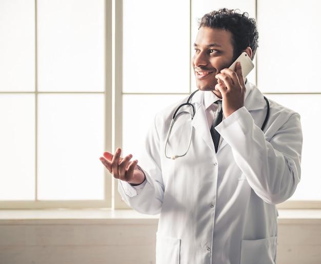Docteur en blouse blanche parle au téléphone. Photo Premium