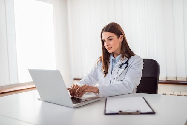Docteur, dactylographie, rapport, sur, ordinateur portable Photo Premium