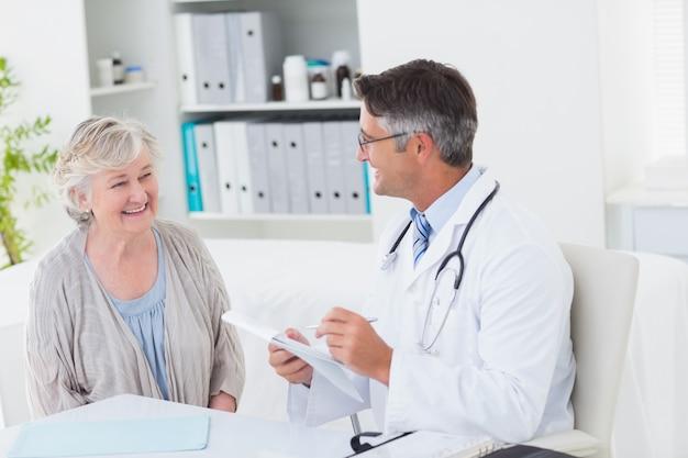 Docteur écrit des prescriptions pour une patiente âgée Photo Premium