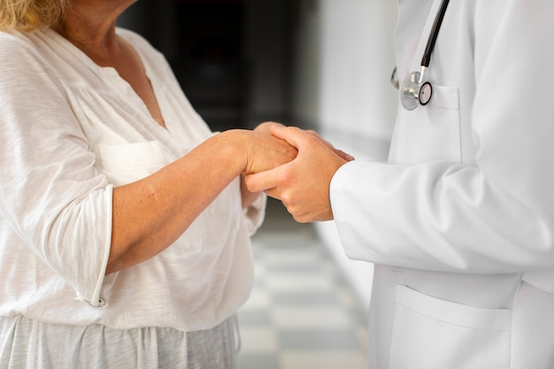 Docteur Mains Tenant Des Mains De Femme Senior Photo gratuit