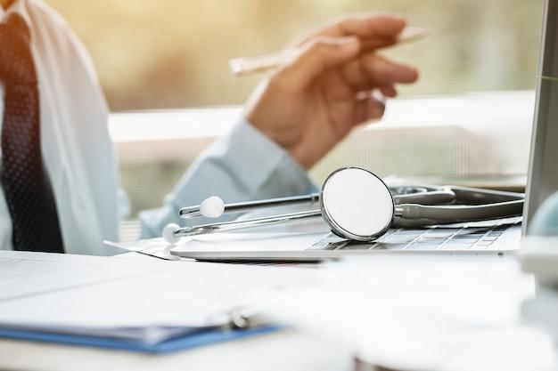Docteur en médecine écrit sur ordinateur portable dans un cabinet médical. Photo Premium