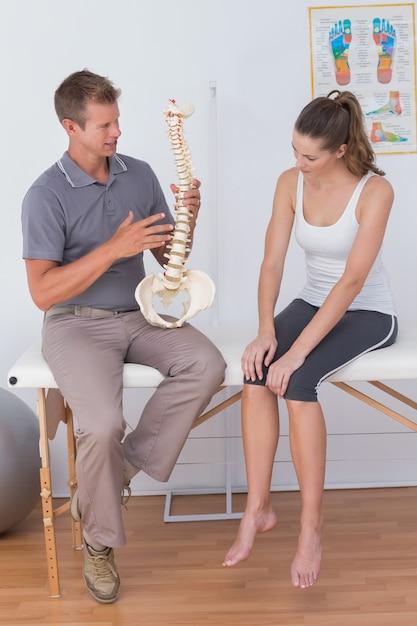 Docteur Montrant La Colonne Vertébrale Anatomique à Son Patient Photo Premium