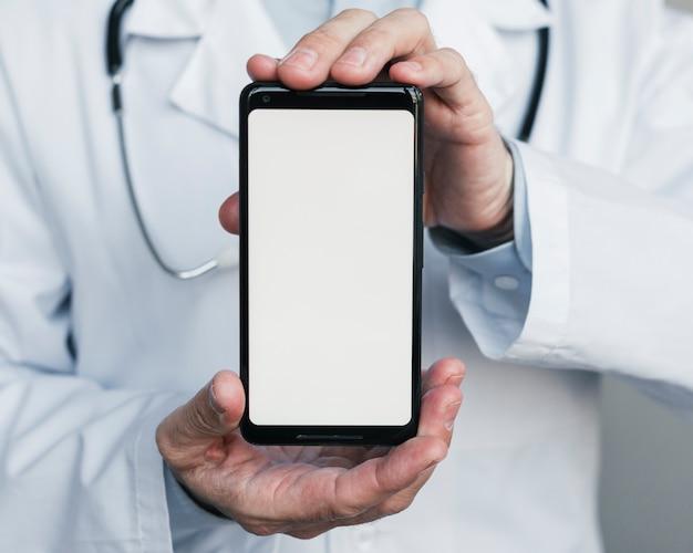 Docteur montrant un téléphone portable Photo gratuit