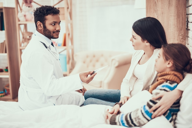 Le docteur prend la température d'une fille avec sa mère enceinte. Photo Premium