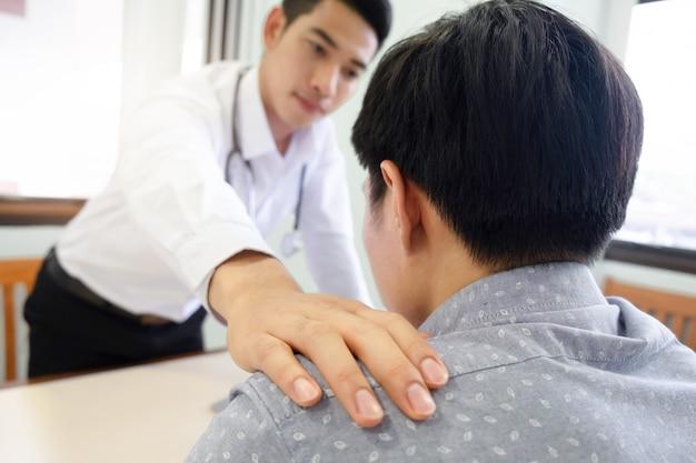 Docteur réconfortant patient au cabinet de consultation. Photo Premium