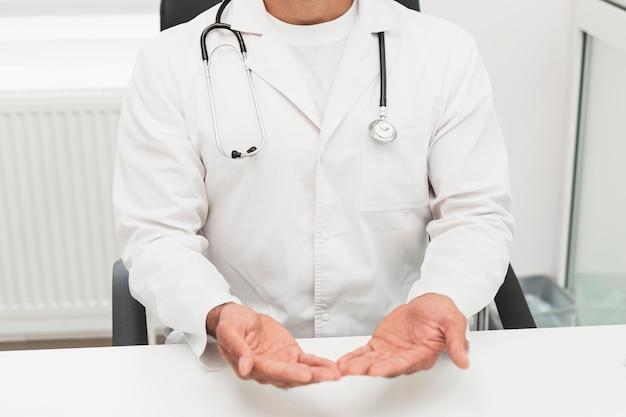 Docteur en robe blanche montrant ses mains Photo gratuit