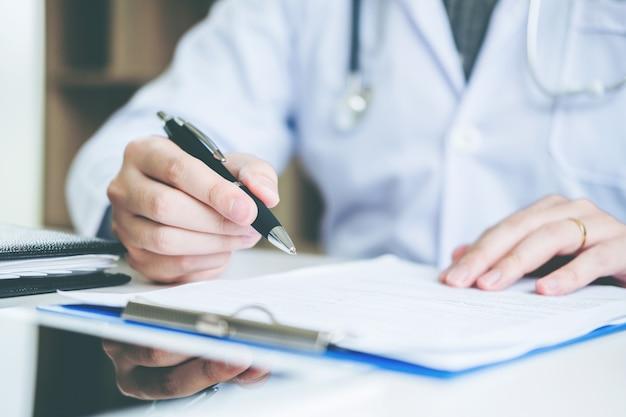 Docteur en tapant l'information travaillant dans le bureau de l'hôpital se concentrant sur le stéthoscope Photo Premium