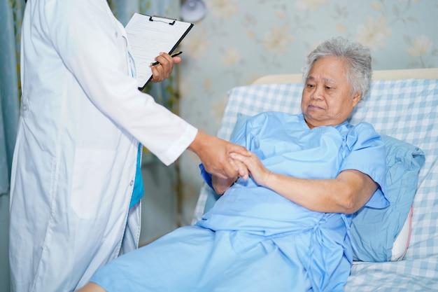 Docteur tenant la main avec une patiente senior asiatique. Photo Premium