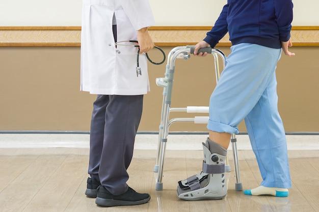 Docteur tenant le stéthoscope dans la main, et l'air patient est nécessaire pour utiliser walker Photo Premium