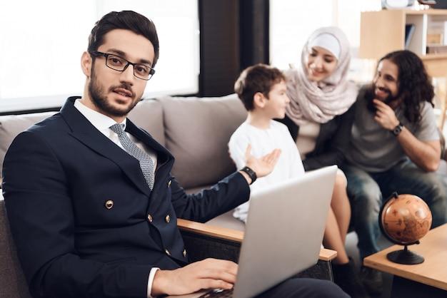 Le Docteur Tient Un Ordinateur Portable Et Pointe Sur Sa Famille. Photo Premium