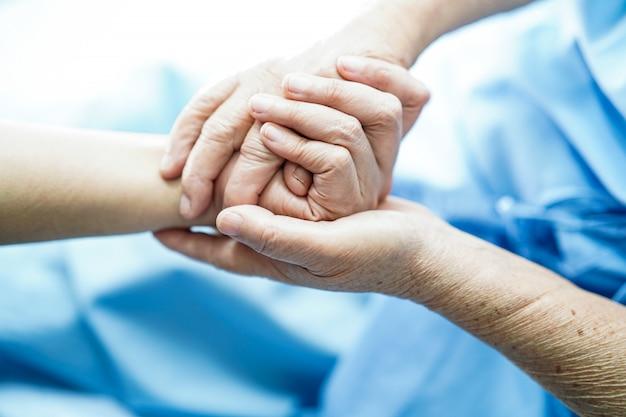 Docteur, toucher, mains, asiatique, vieux, ou, vieille dame, patient, femme, à, amour Photo Premium