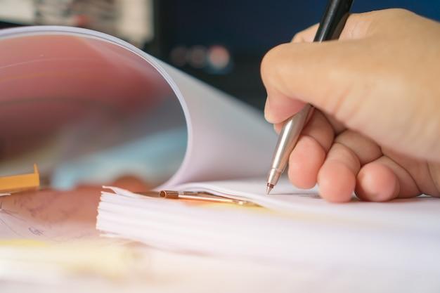 Document de rapport et affaires en cours concept: gestionnaire d'hommes d'affaires vérifiant et signant des documents de rapports avec une calculatrice, un ordinateur portable sur des piles de fichiers dans un bureau moderne. Photo Premium