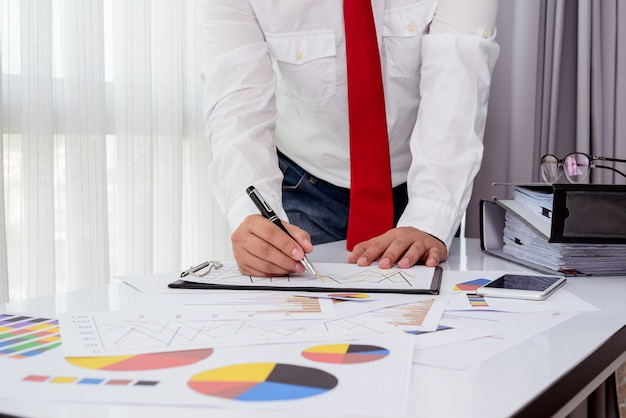 Documents d'affaires sur la table de bureau avec smartphone et tablette numérique et homme travaillant Photo Premium