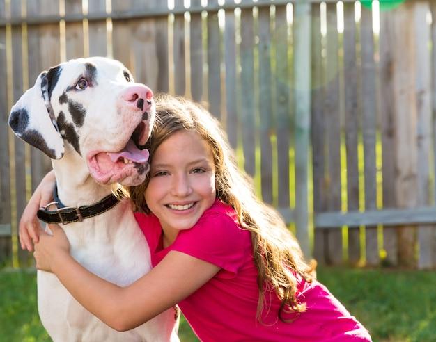 Dogue et kid fille câlin jouer en plein air Photo Premium