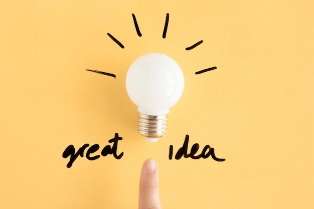 Doigt humain pointant vers l'ampoule avec un excellent texte d'idée Photo gratuit