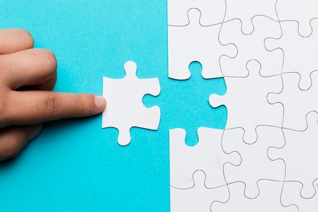 Doigt humain touchant un morceau de puzzle blanc sur fond bleu Photo gratuit