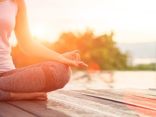 Doigt de yoga femme agissant sur les mains devant la mer avec la nature environnante fond Photo Premium