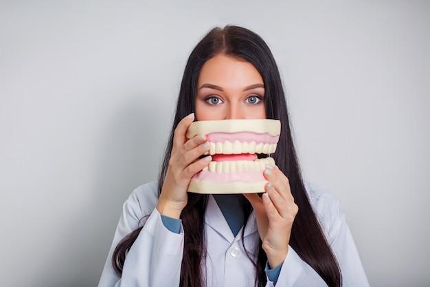 Doktor de belle jeune dentiste tenant une prothèse plastique dans une boîte. Photo Premium