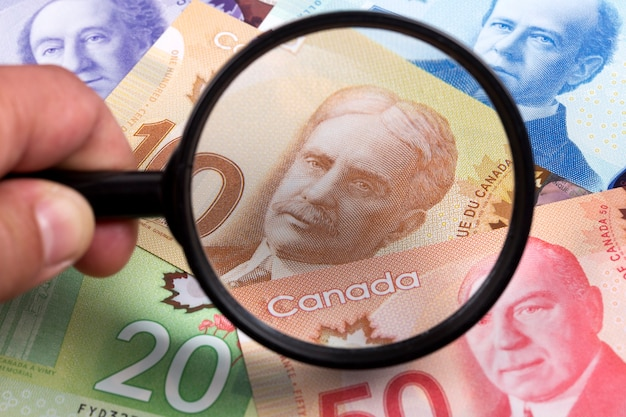 Dollars Canadiens Dans Un Fond De Loupe Photo Premium