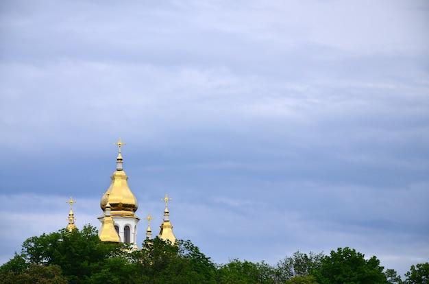 Dômes dorés d'une église orthodoxe au milieu des arbres en fleurs sur fond de ciel bleu nuageux Photo Premium